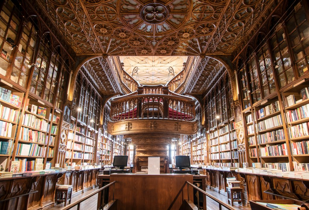 Inside of a library with brown paneling, high ceilings and multiple shelves of books.