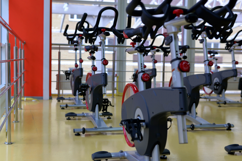 Multiple exercise bicycles inside a gym.