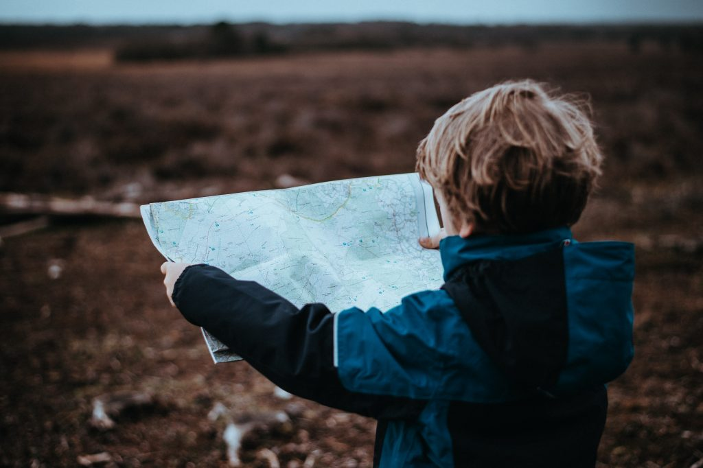 Small child looking at map wearing a blue and black jacket facing towards the horizon.