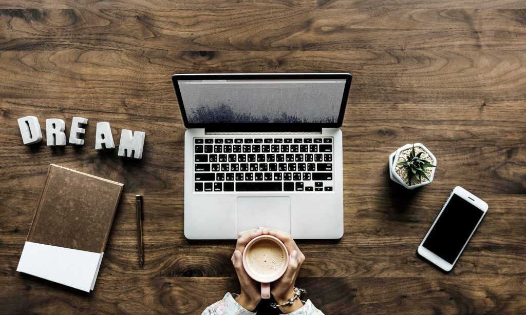 A brown desk where a student sits grasping a coffee mug in front of a lap top with a brown notebook, pencil, cell phone, small green plant and a DREAM sign