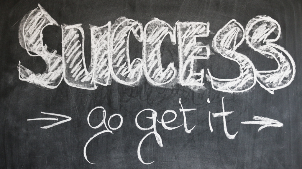 Blackboard with white chalk writing that says Success Go Get It