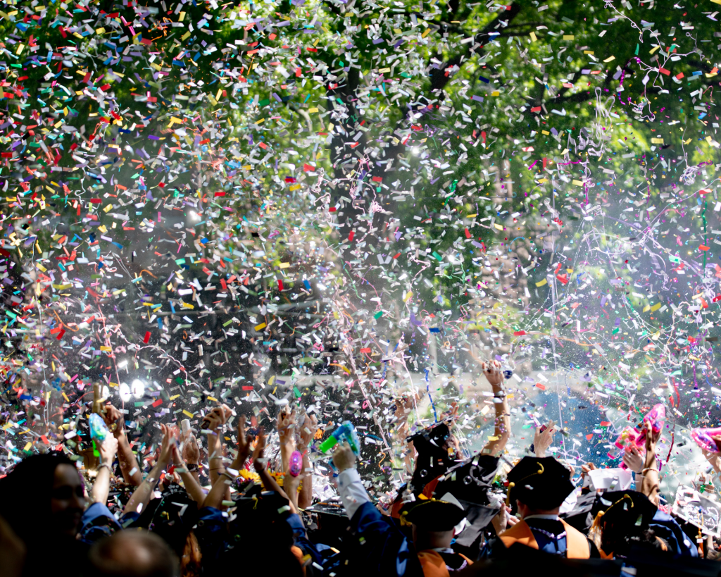 Graduating class celebration with graduates' arms in air with multi-colored confetti flying in air.