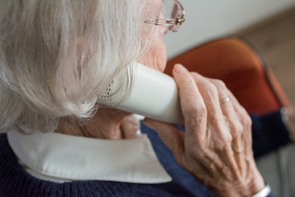 An elderly lady with glasses sitting in a chair talking on the telephone.