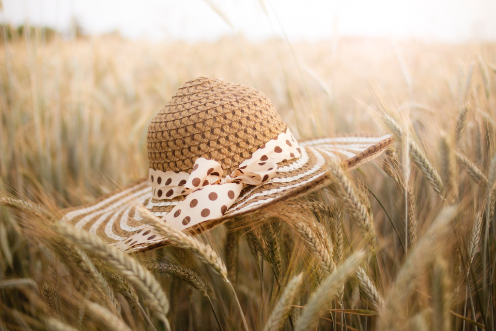 Straw hat laying on top of wheat field with sunlight in background