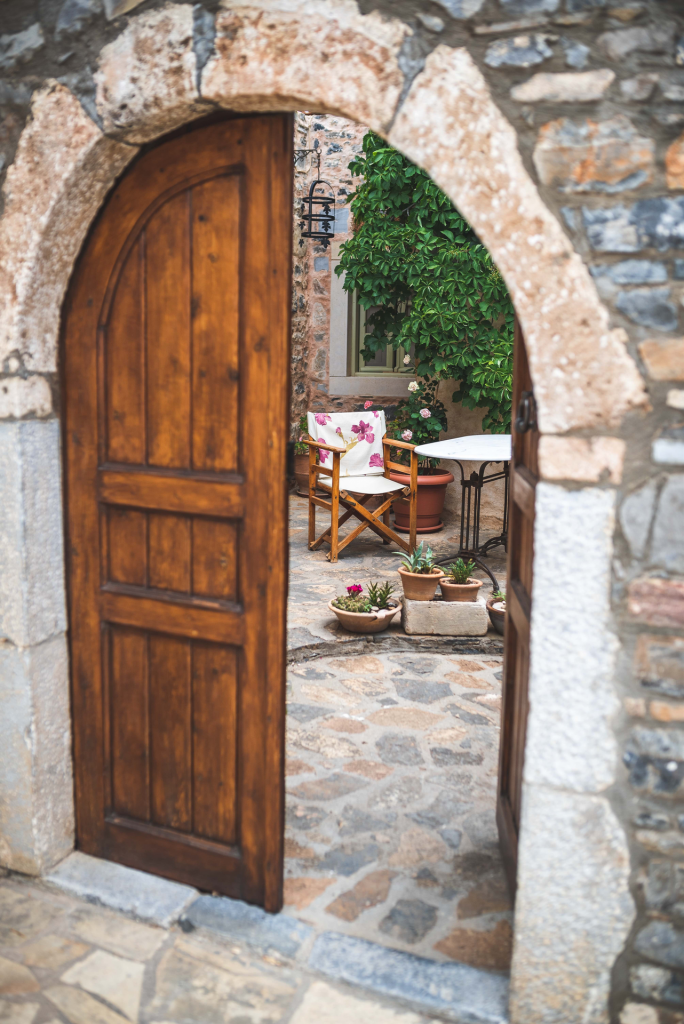 Stone arch opening with two wood doors with one wood door opening up into stone courtyard containing plants, flowers and table and chair.