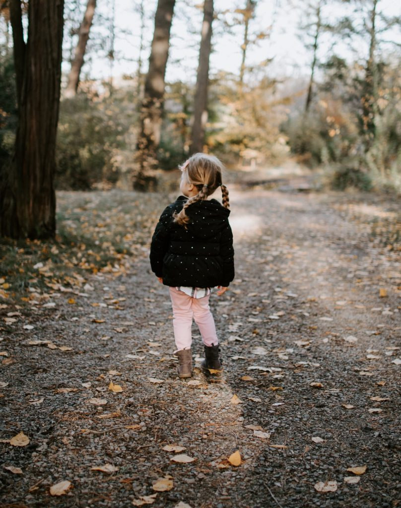 Little girl with braided pigtails strolling down dirt road looking out at the woods.