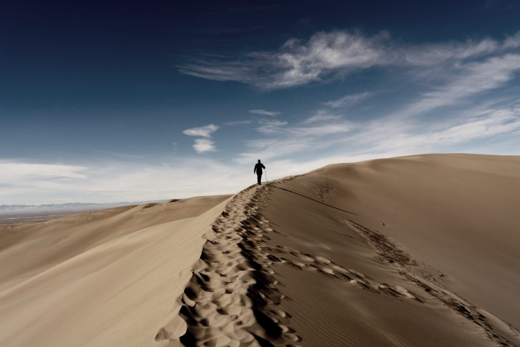 person walking uphill in deep sand