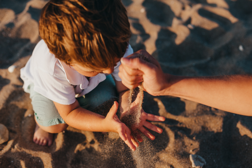 Toddler boy crouched on beach holding hands open to catch sand coming from mother's hand