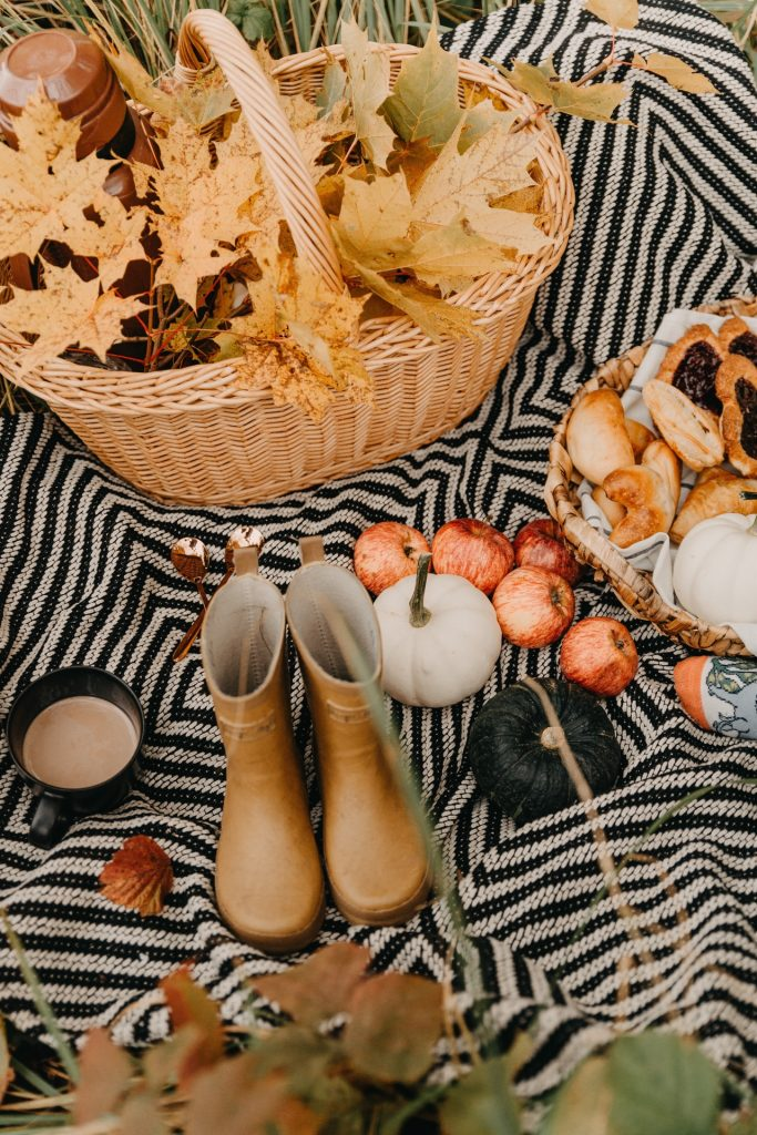 Fall collection with basket of leaves, tan colored boots, orange pumpkins and tray of pastries