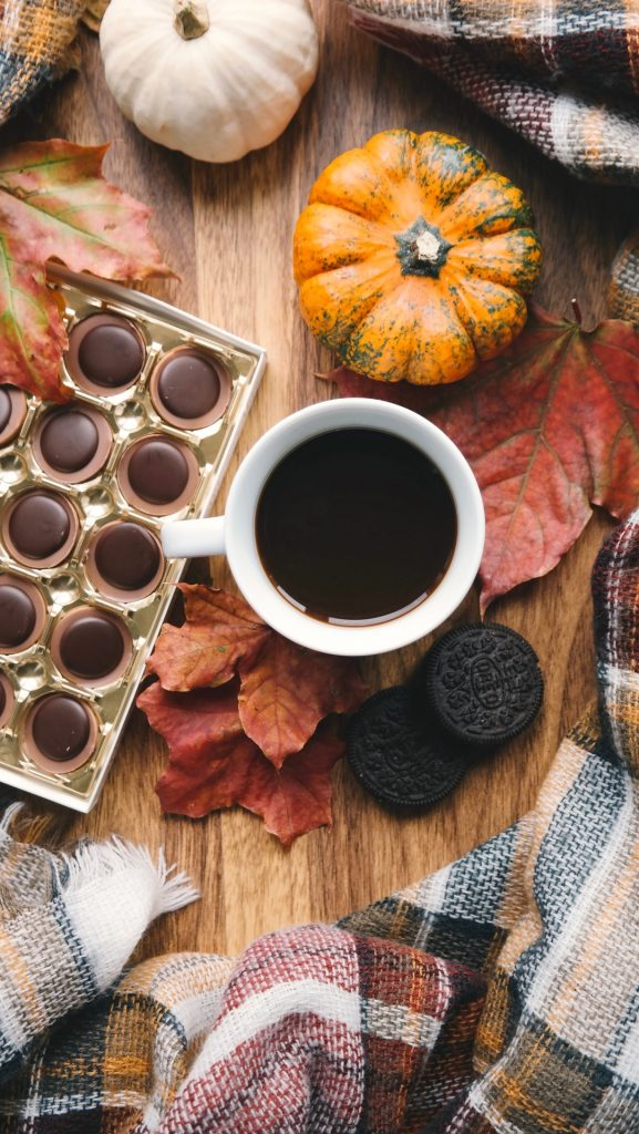Close up of fall collection of box of chocolates, cup of coffee, Oreos and fall leaves