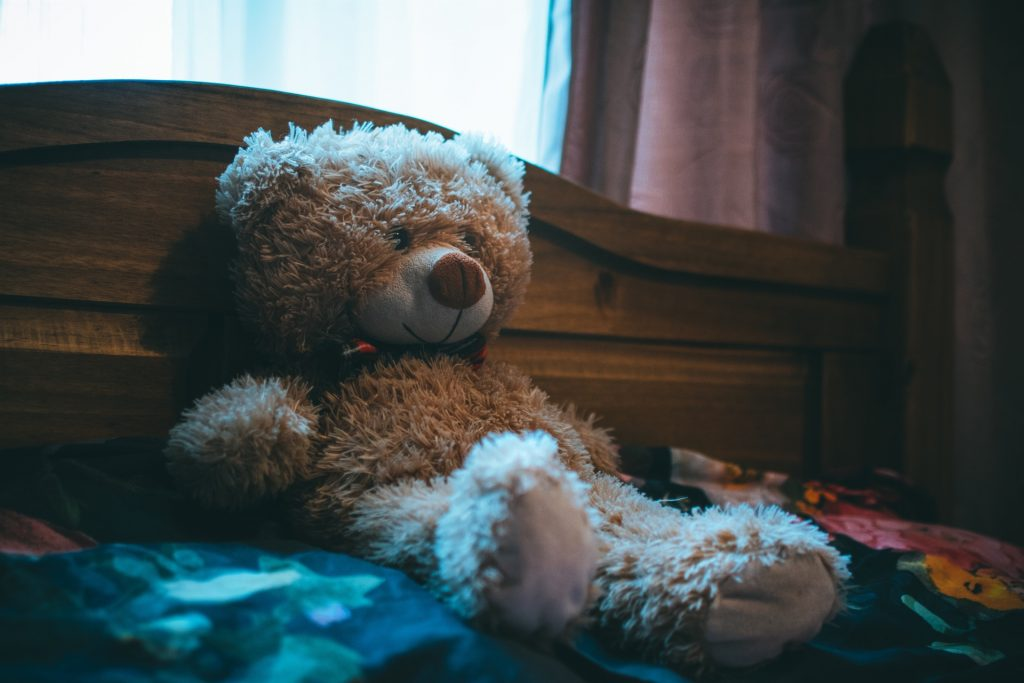 Brown teddy bear leaning up against headboard of bed