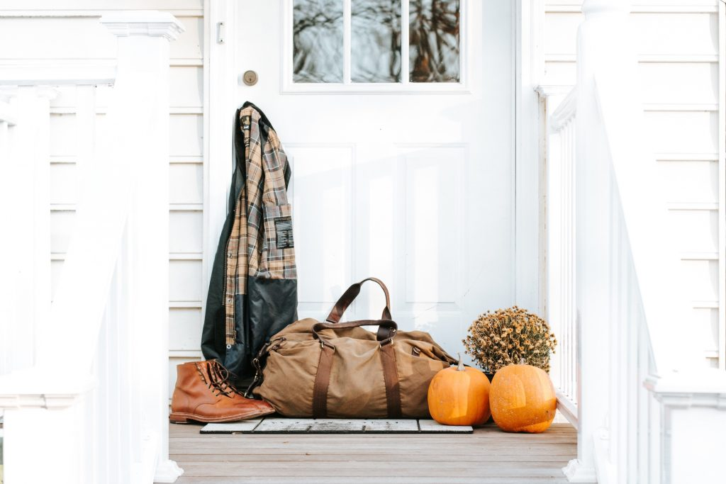 White door and entryway with duffle bag, jacket, books and pumpkins