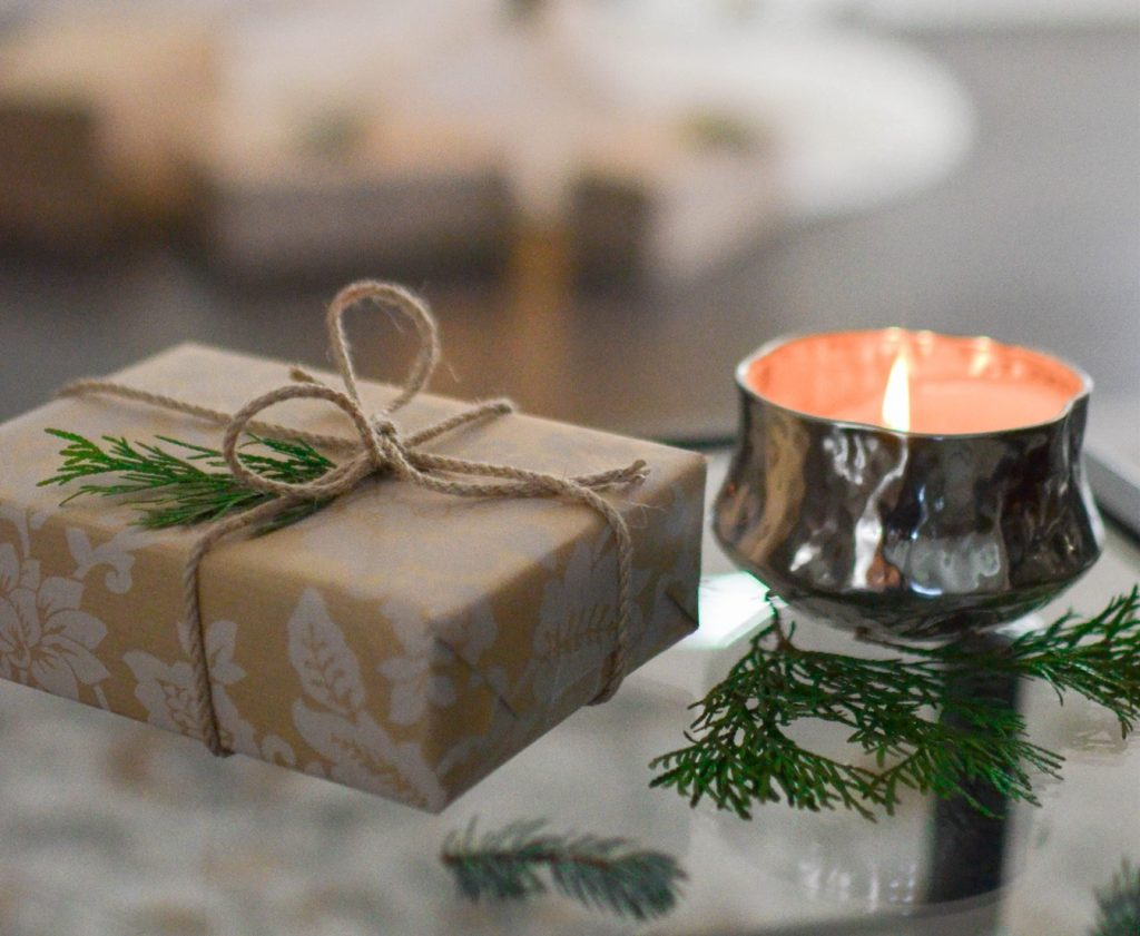 Close up of small holiday package with lit candle
