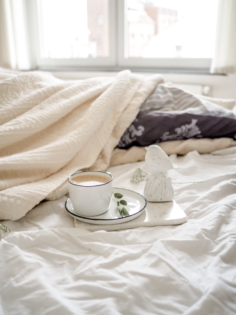 Bed with white and cream colored blankets with cup and saucer