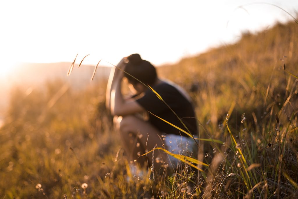 Woman sitting on grassy hillside with blurred sunlight in distance