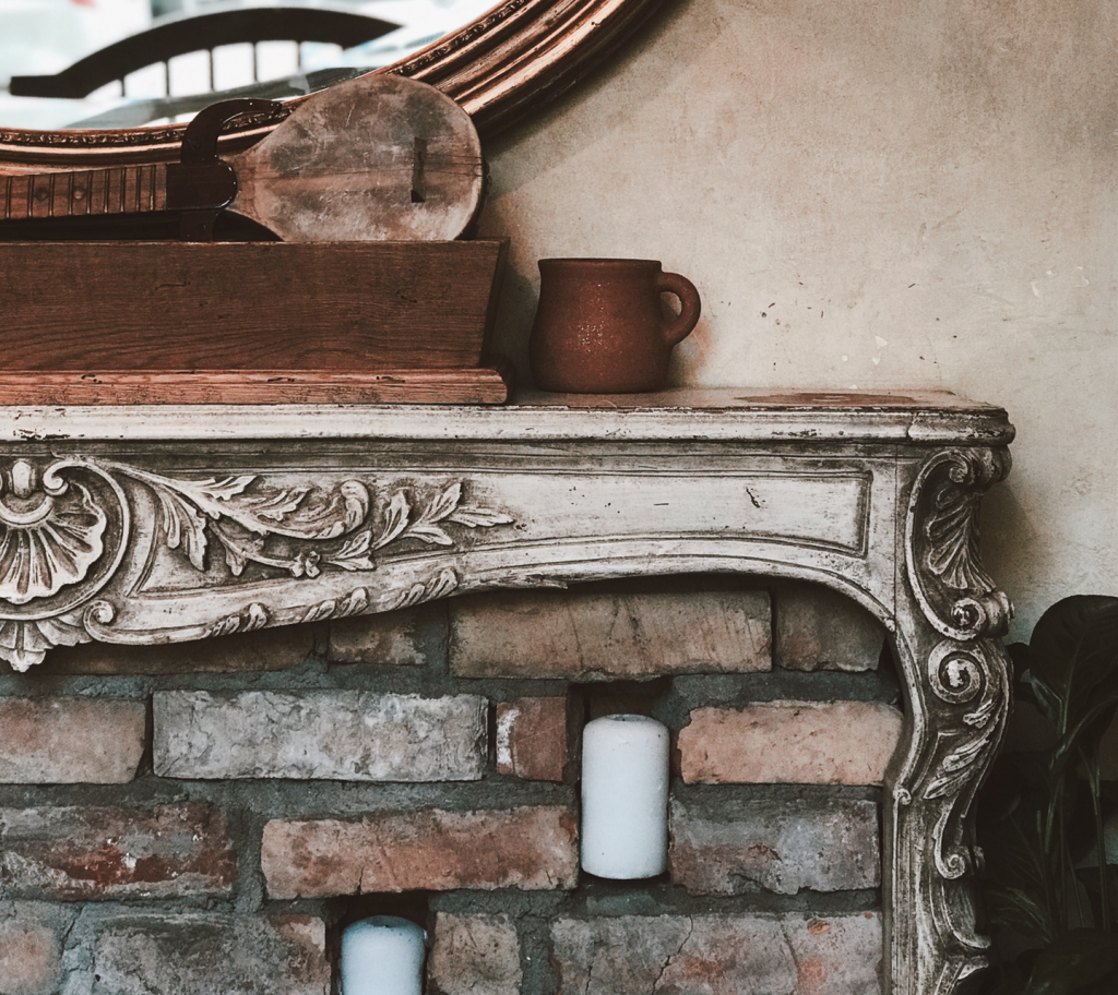 Brick fireplace and ornate wood mantle with mug and wood box with mirror in background