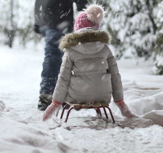 Little girl sitting on sled in snow wearing a pink beanie hat with light pink pom pom