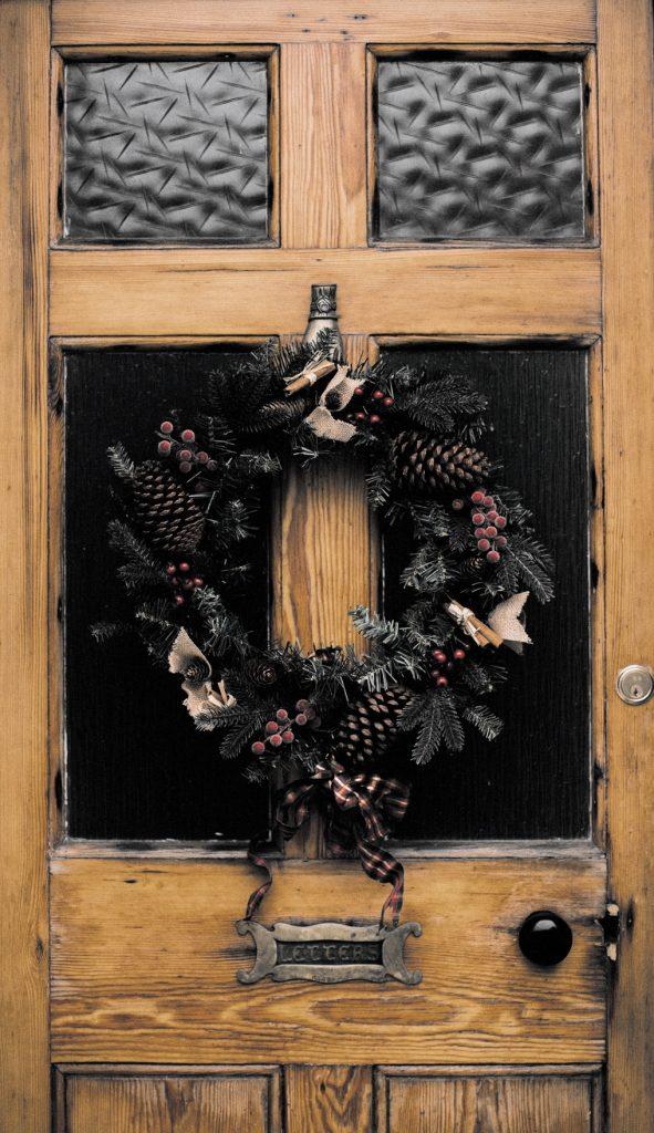 Close up of green wreath on old brown door