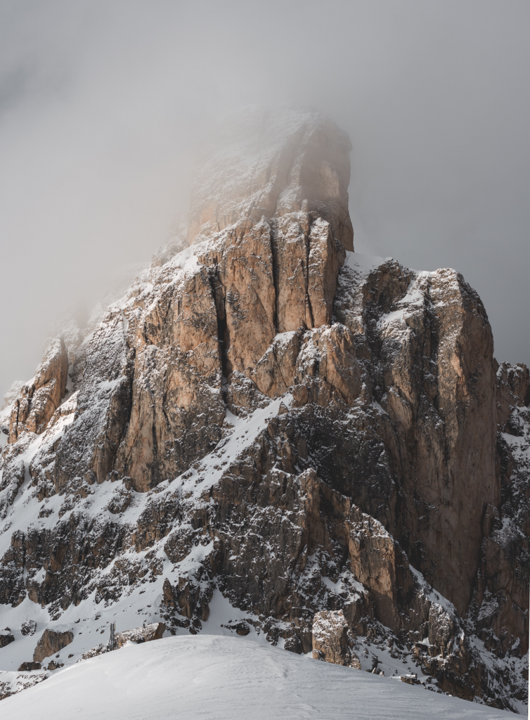 Mountain with snow in clouds and fog