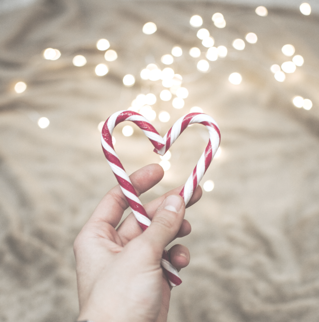 Close up of candy cane heart with gold lights in background