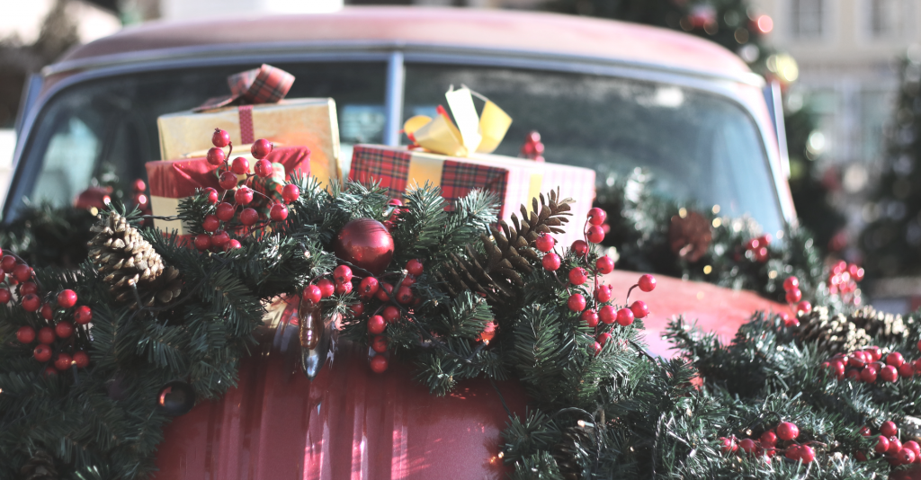 Back end of old red car with Christmas packages and green garland and red berries on top