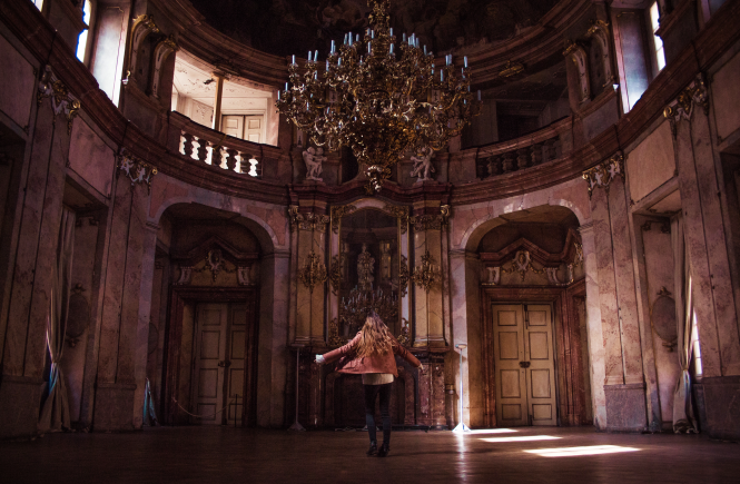 Woman dancing in ballroom with chandelier