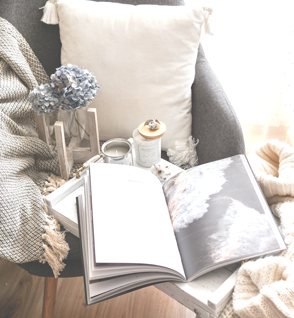 Chair with white pillow and blanket with side table with book and blue flower