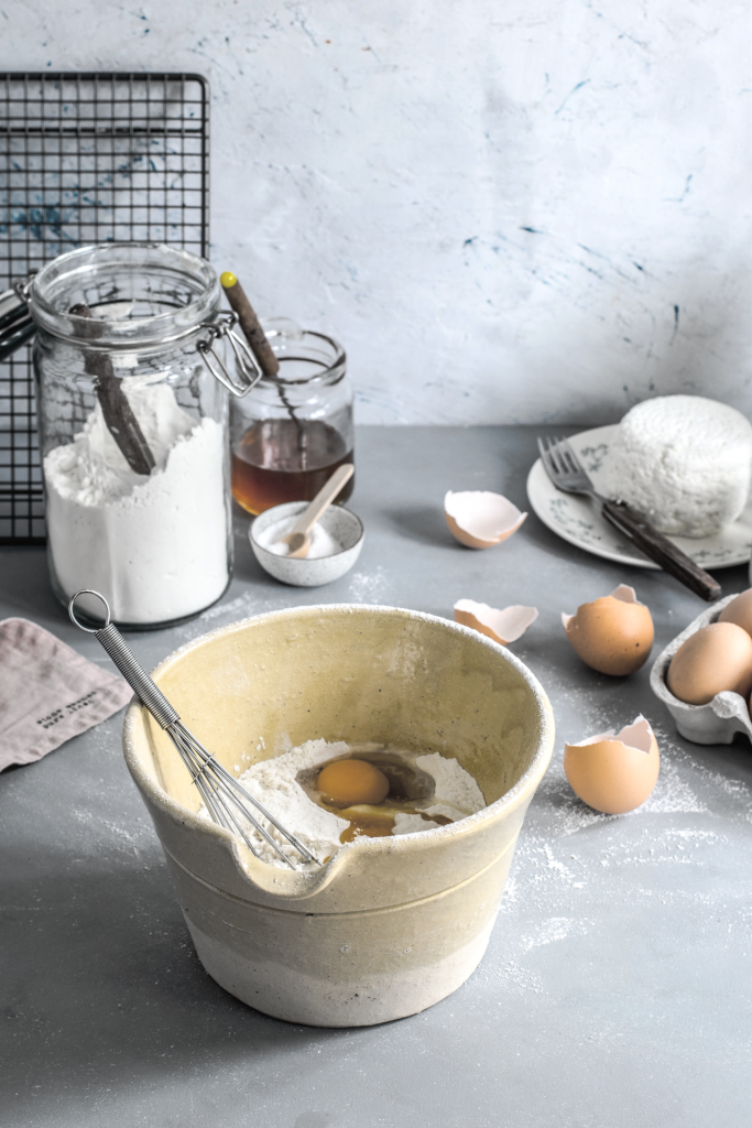 Kitchen counter with baking items including eggs and flour and bowl