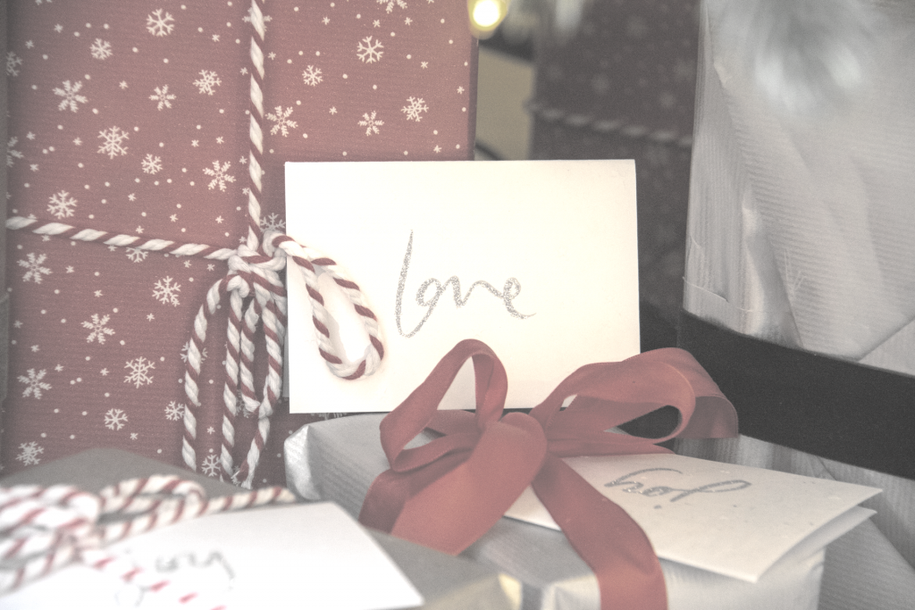 "Wrapped present with ""Love"" tag with red ribbon"
