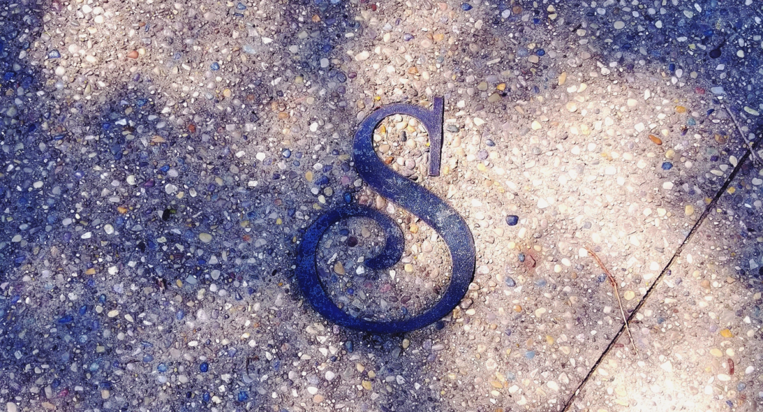 "Close up image of ""S"" on a sidewalk with a pair of feet in tennis shoes"