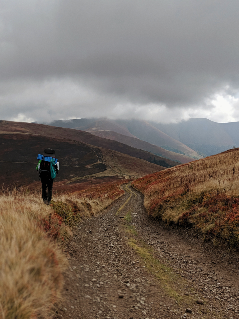 Hiker on desolate gravel road heading towards mountains and grey skies.