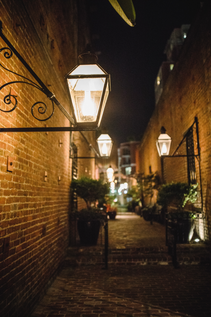 Multiple lit lamps in brick alley at night