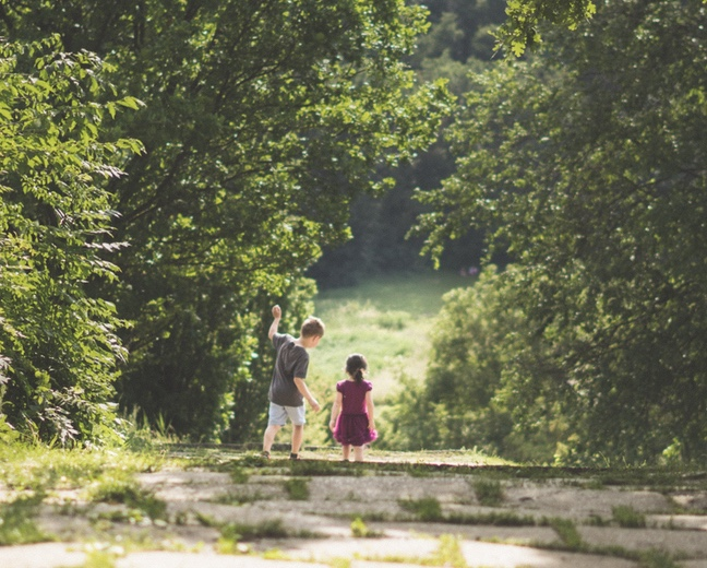 Little boy and girl walking down a road into the green trees