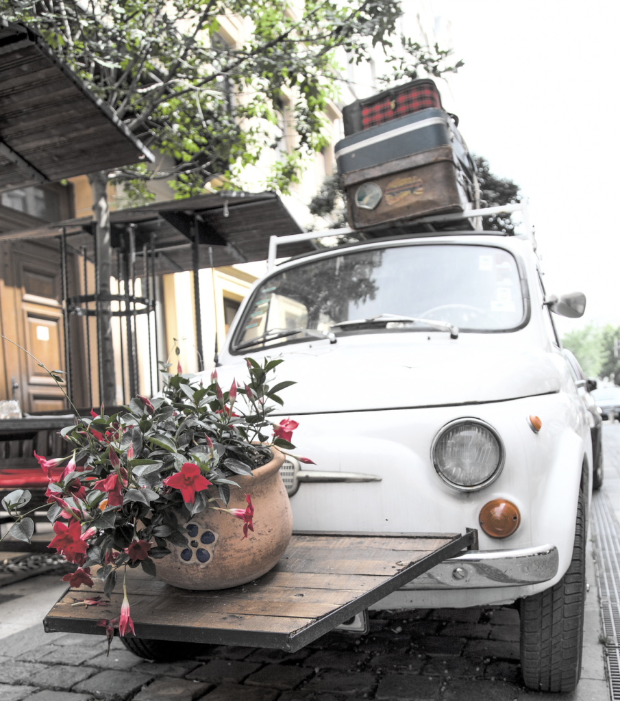 White car with multiple suitcases on top and a flower pot hanging on the front end