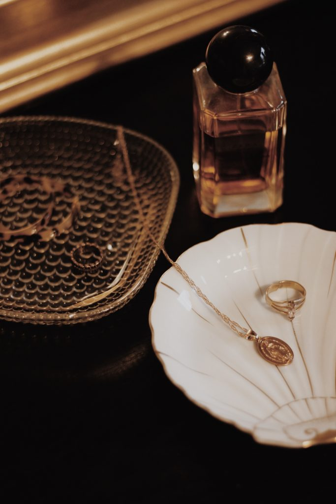 Close up image of gold jewelry and perfume.