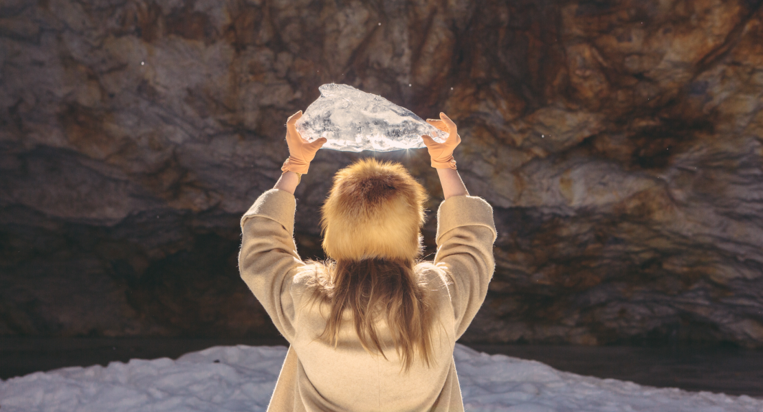 Woman holding block of ice up to sky.