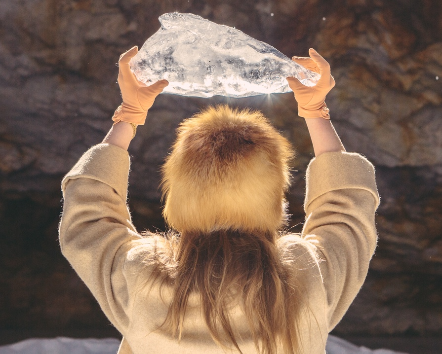 Woman holding up large chunk of ice up to the sunshine.