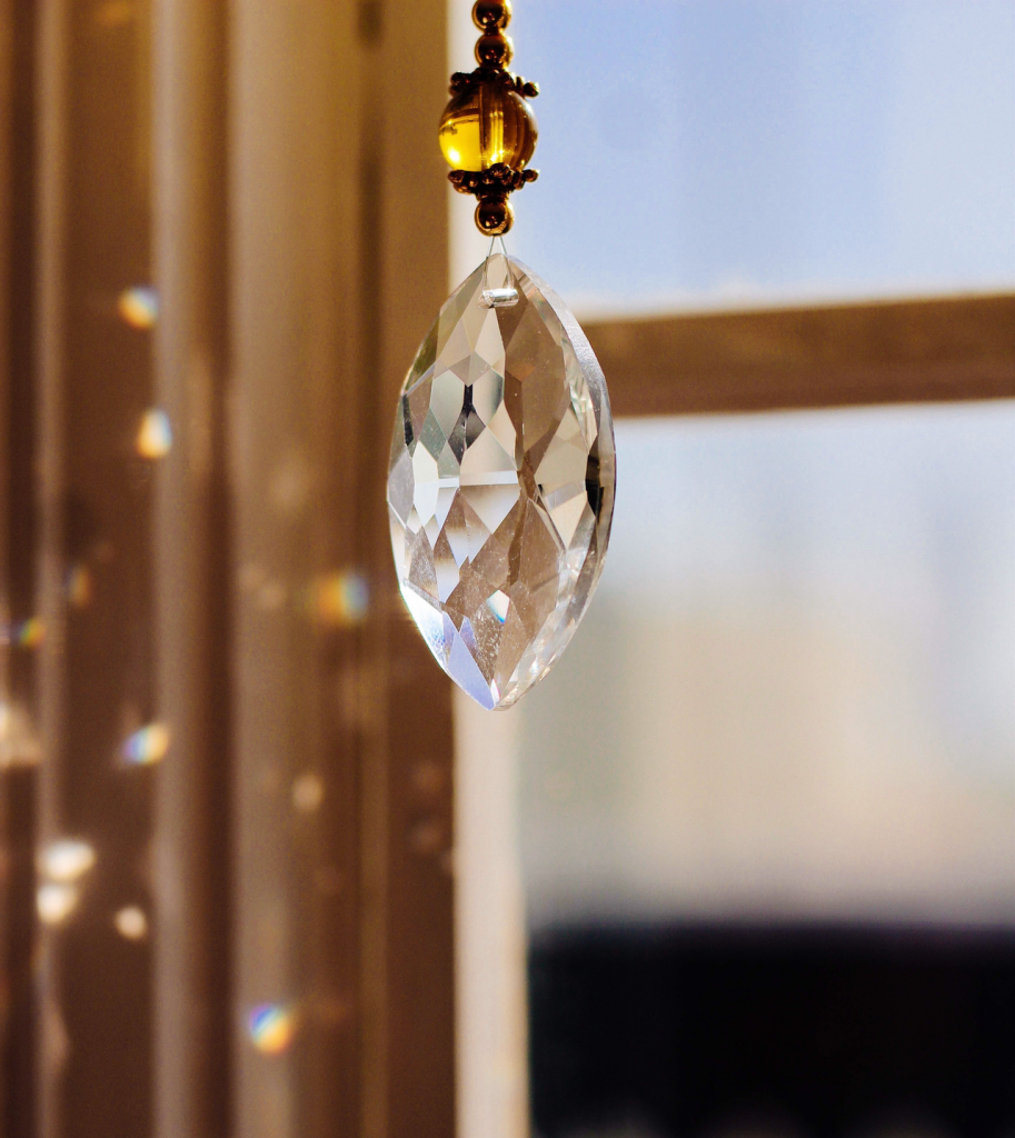 Close up image of crystal hanging in front of a window with specks of gold refection in background