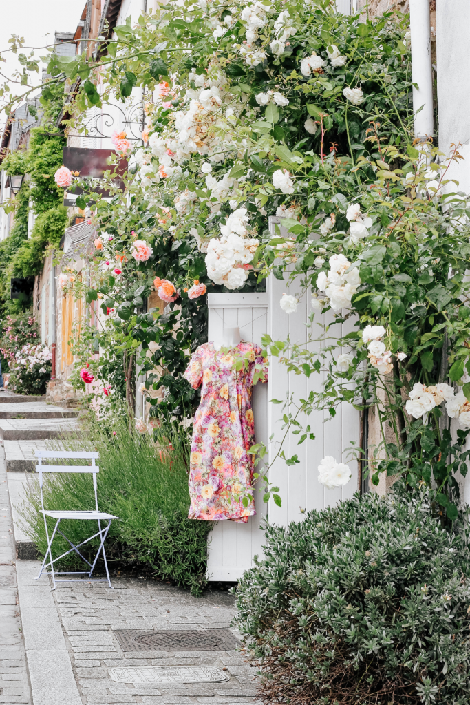 Side view of multiple boutiques with climbing roses, patio chair, and floral pink/orange summer dress hanging up