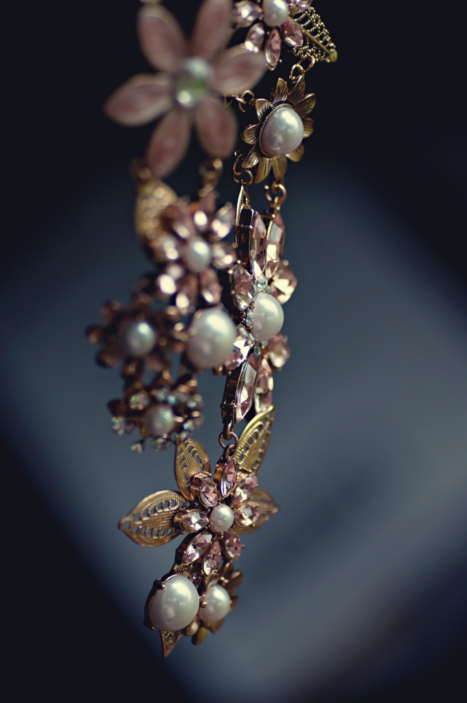 Dangling necklace of pearls, gold ornate flowers with light pink jewels.