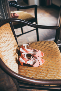 Close up image of orange sandals sitting on top of a brown/tan chair
