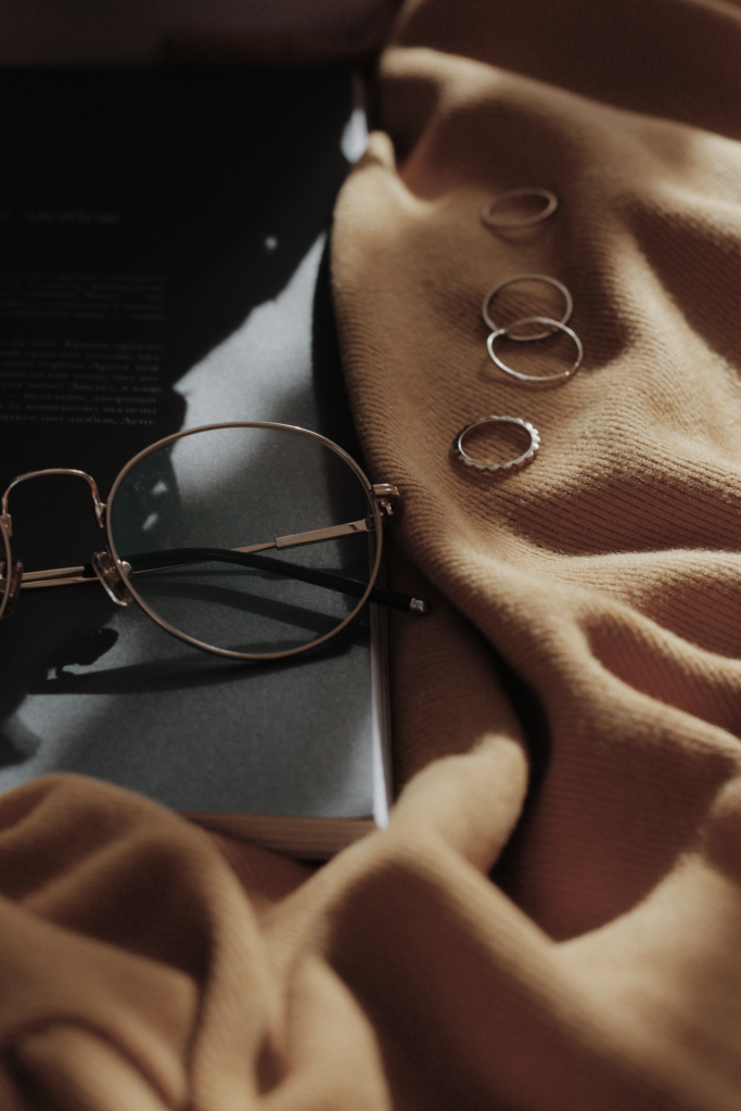 Close up image of reading glasses, gold rings on top of light tan blanket.
