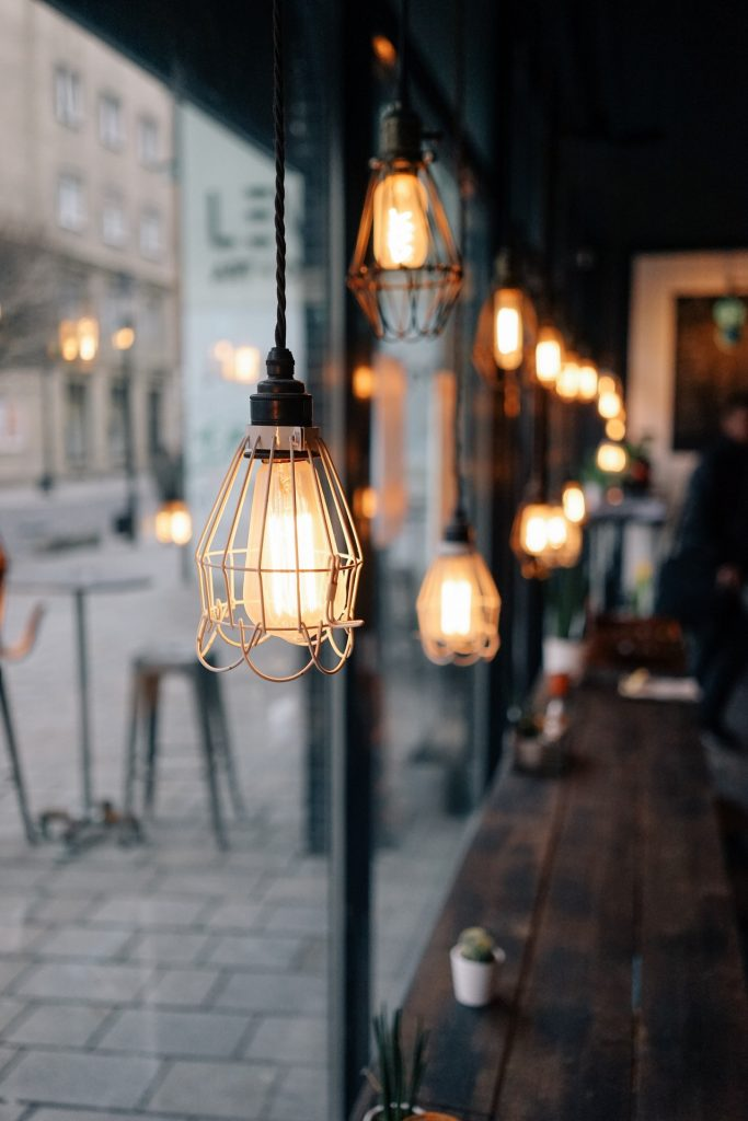 Multiple gold hanging lights inside a cafe set up against a window facing outside