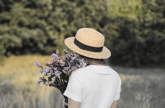 Woman with straw hat holding bouquet standing in field