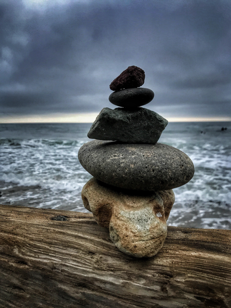 Five beach rocks stacked on top of one another on driftwood with sea in background