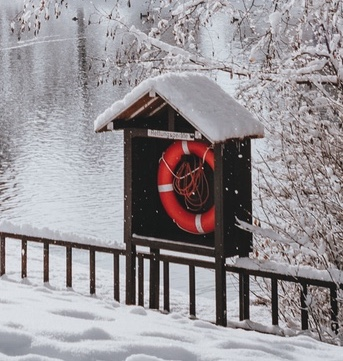 Red lifesaver next to a lake in winter