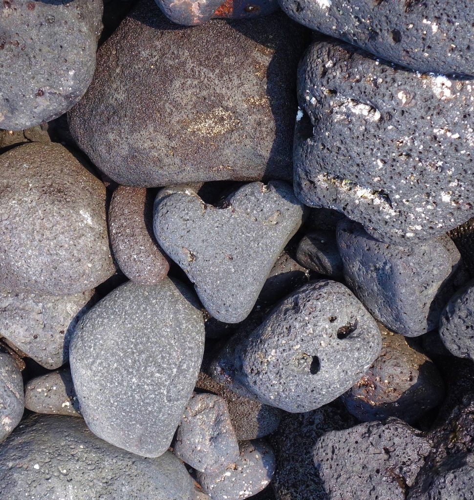Close up image of beach rocks with one heart shaped beach rock