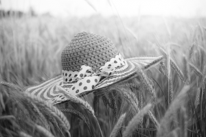 Straw hat in wheat field (black and white photo)