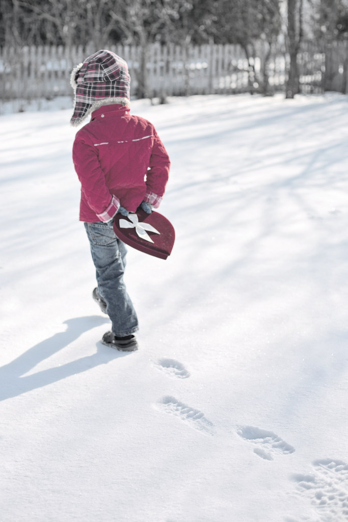 Small boy, wearing red winter jacket, carrying a red valentine box behind his back walking in snow
