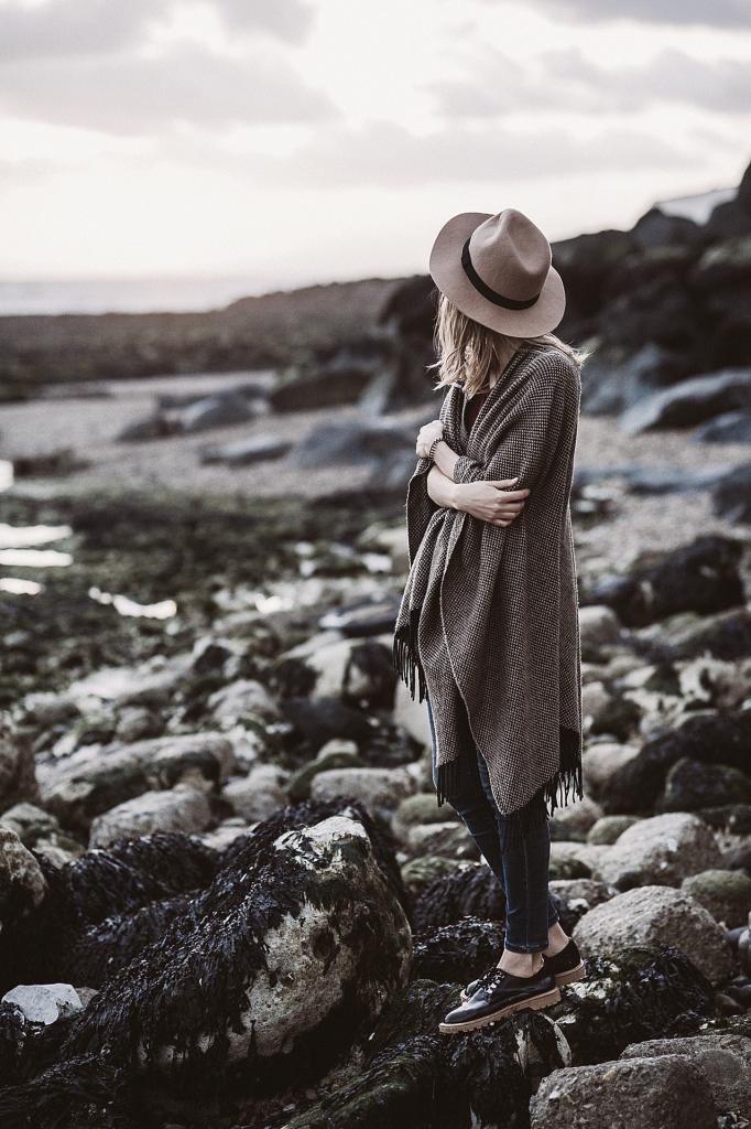Woman wearing straw hat standing on rocky beach
